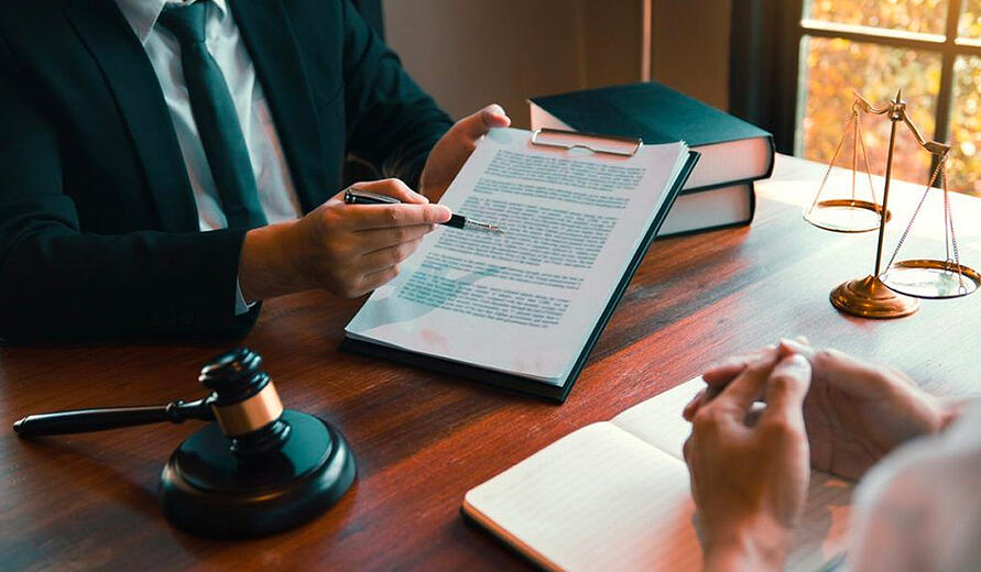 Divorce Legal showing document to client while sitting at boardroom style desk