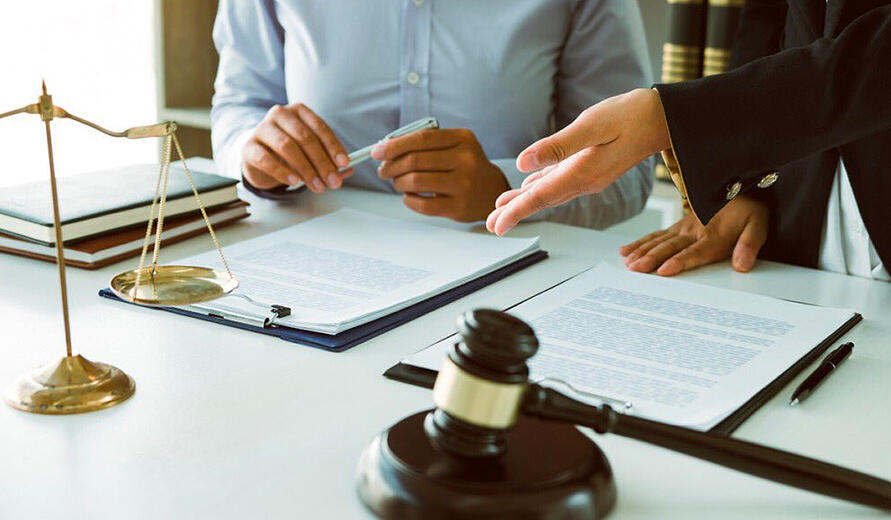 Divorce Lawyer preparing client for court with documents and gavel