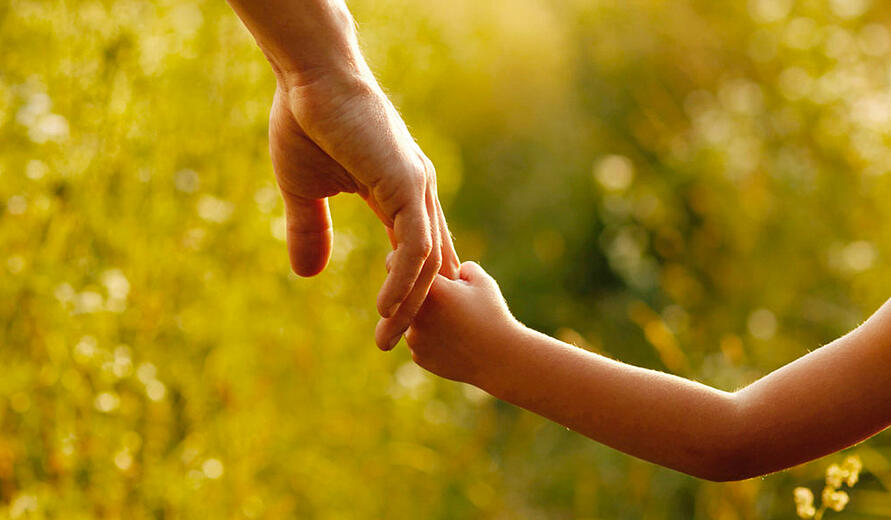 Father holding childs hand with bokeh fall background