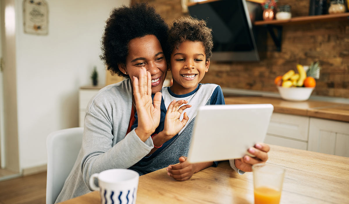 African American mother and son waving during video call at home