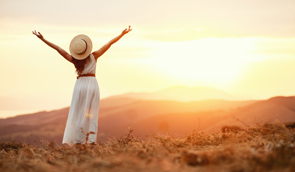 Happy woman standing with arms in the air in front of sunset
