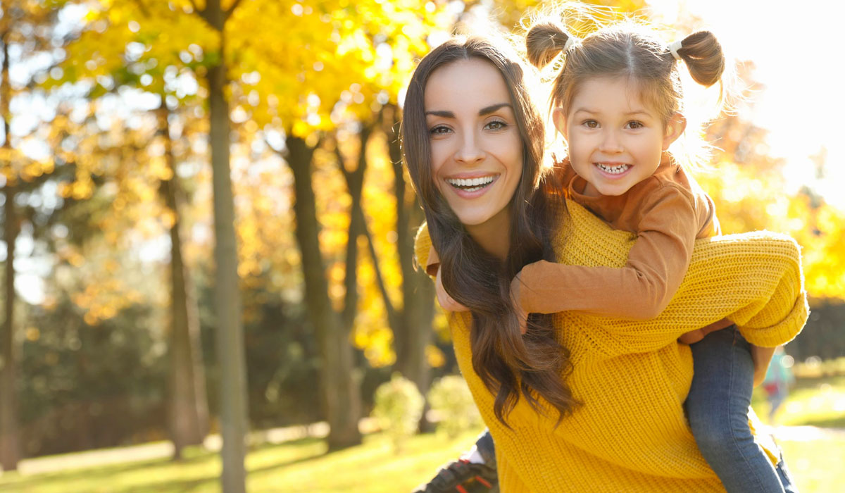 Happy woman with little daughter walking in the park during Autumn