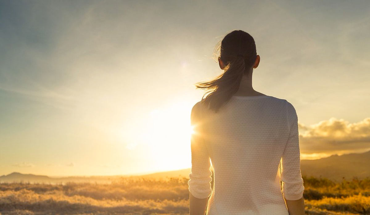 Woman standing looking at sunrise