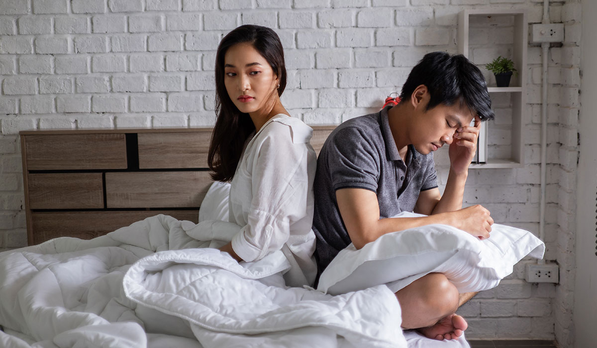 asian couple mad at each other sitting on bed