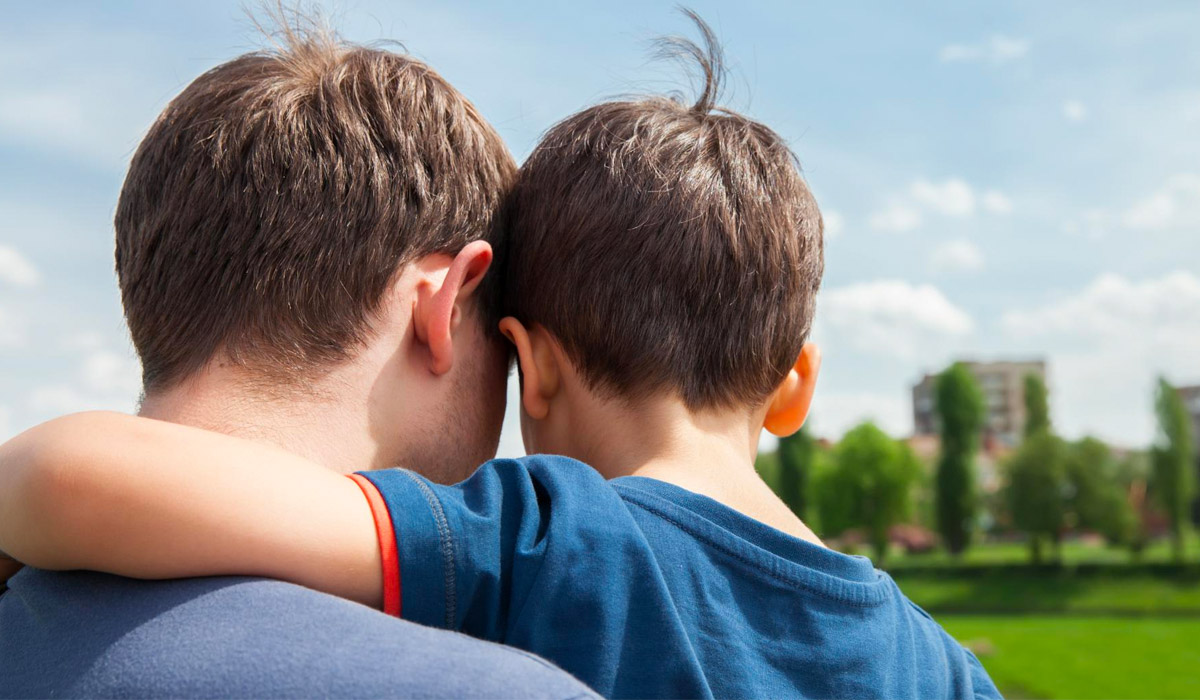 back view of dad hugging son at the park