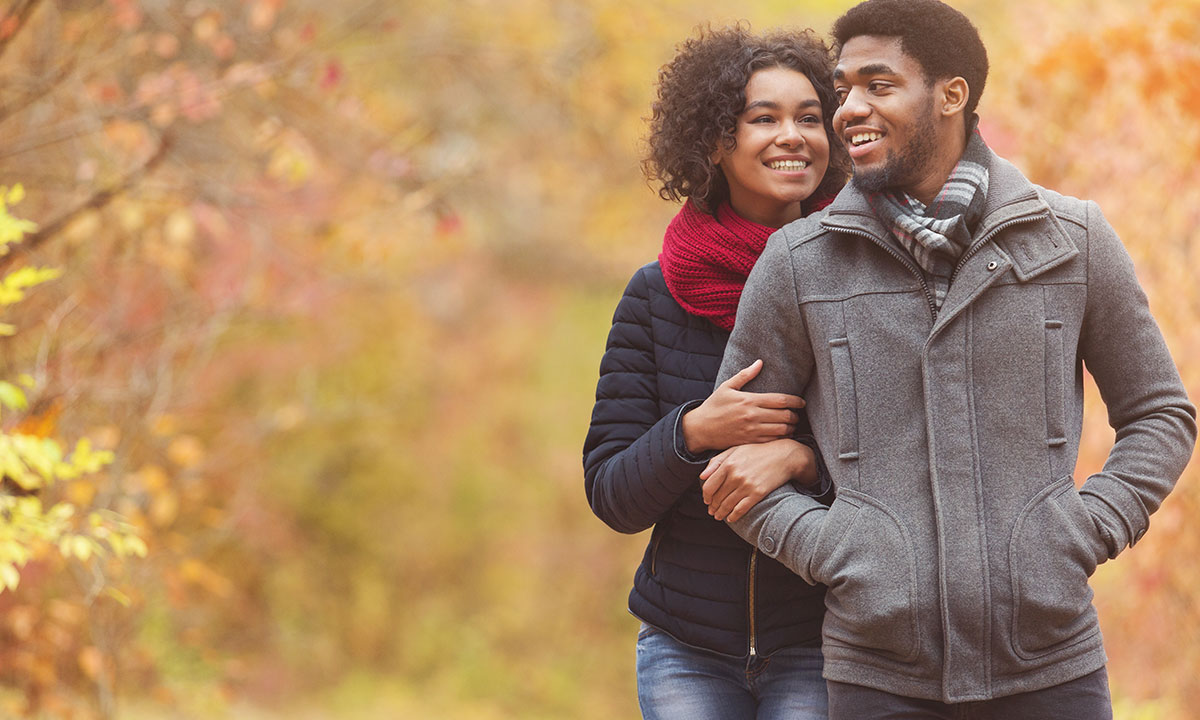 black couple walking with fall leaves in the background