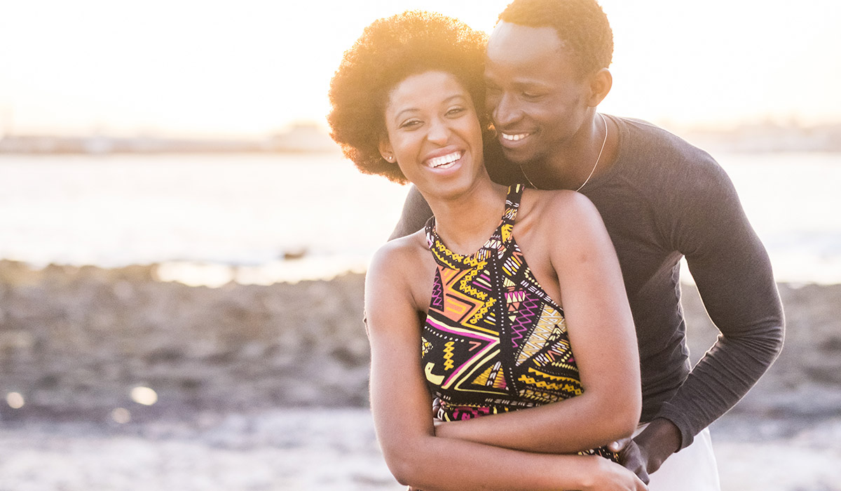 black race african american couple embracing outdoors on the beach