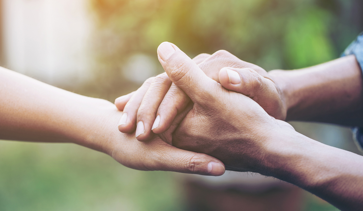 close up of man and woman holding hands