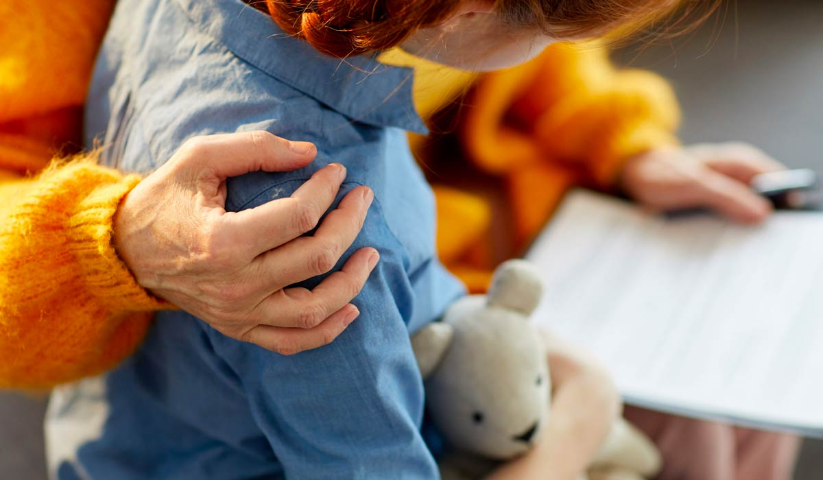 close up shot of girl holding stuffed animal while being hugged by parent