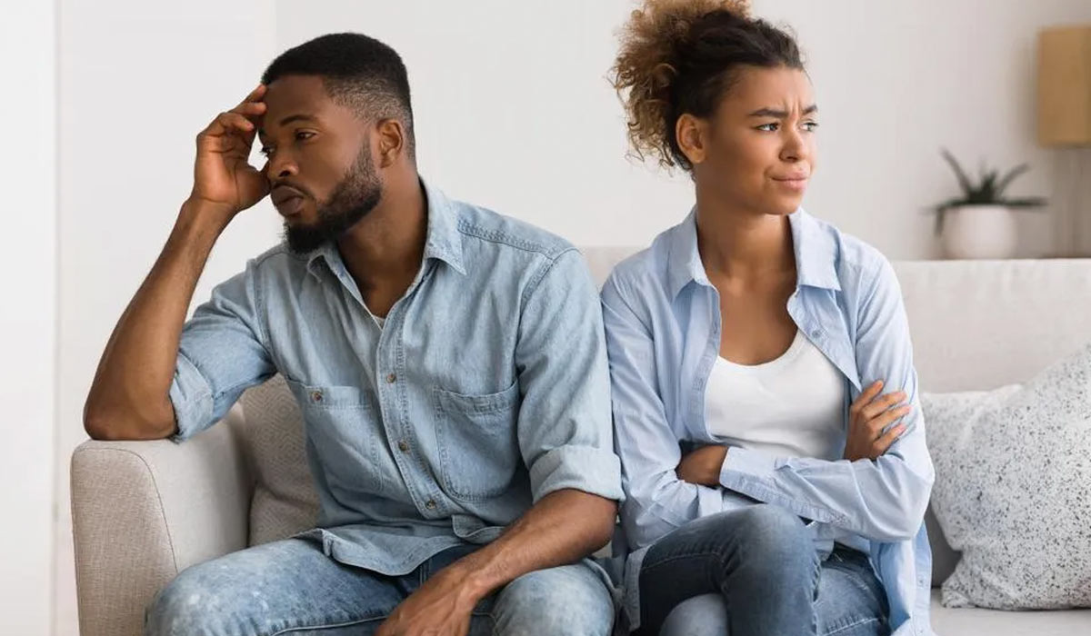 couple looking unhappy sitting on couch