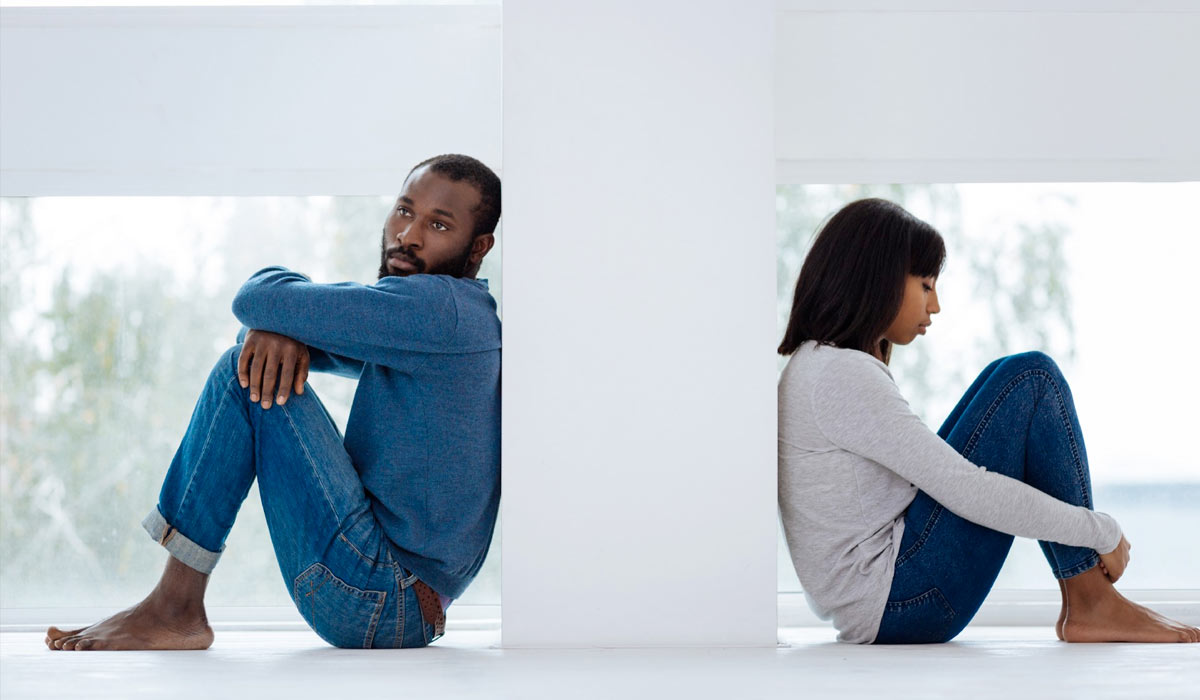 couple sitting on the floor looking sad and separated by a wall