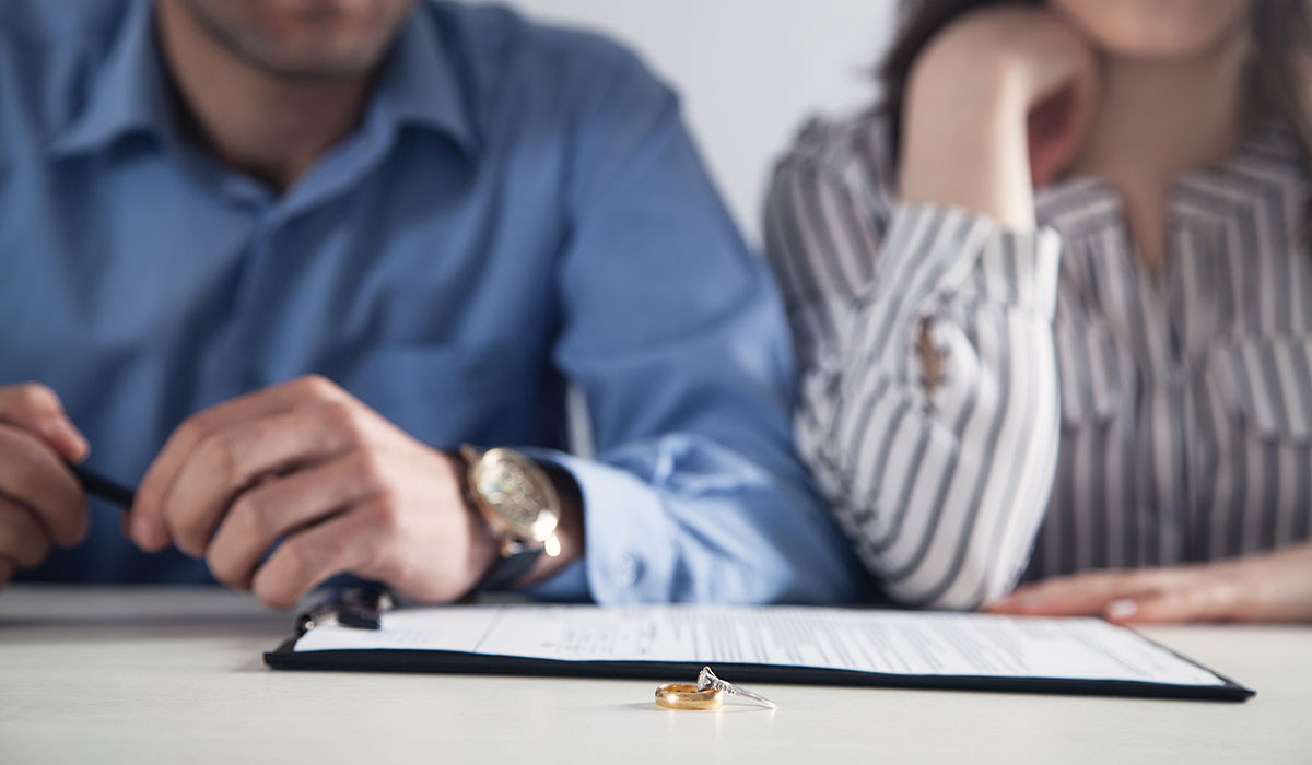 Couple with divorce contract and ring on desk