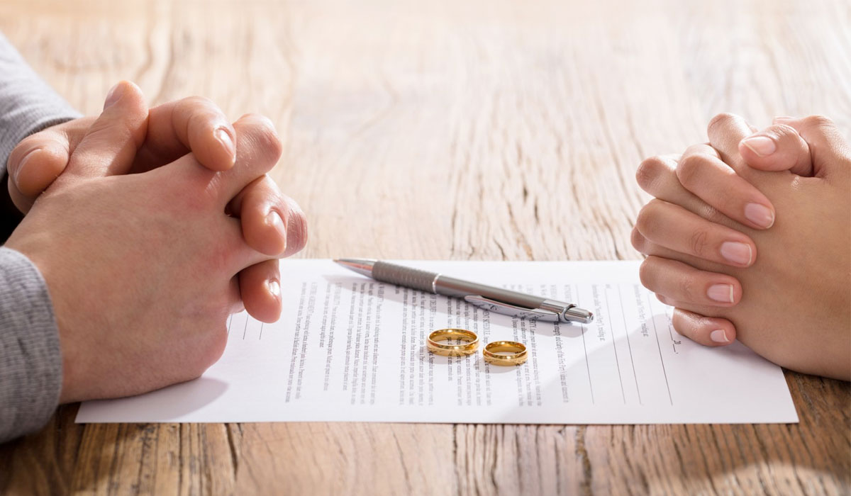 couples hands on divorce papers