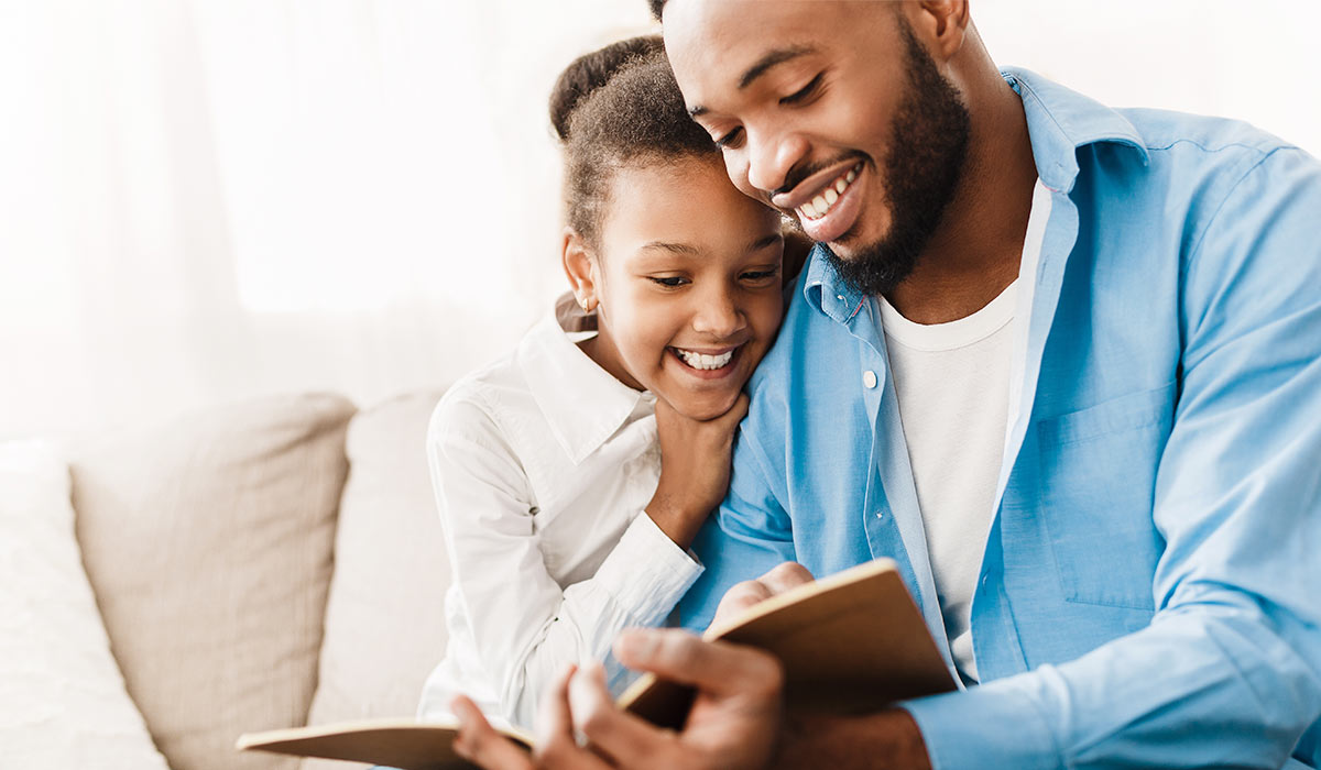 dad and daughter enjoying a book together