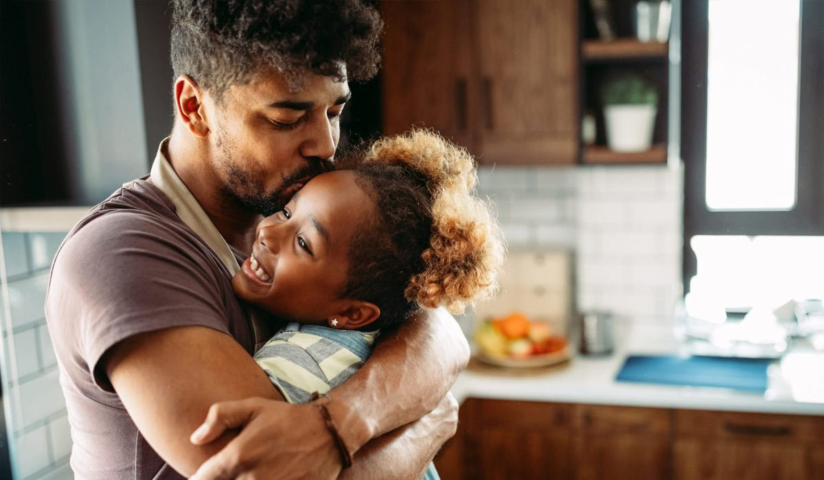 dad embracing daughter in the kitchen