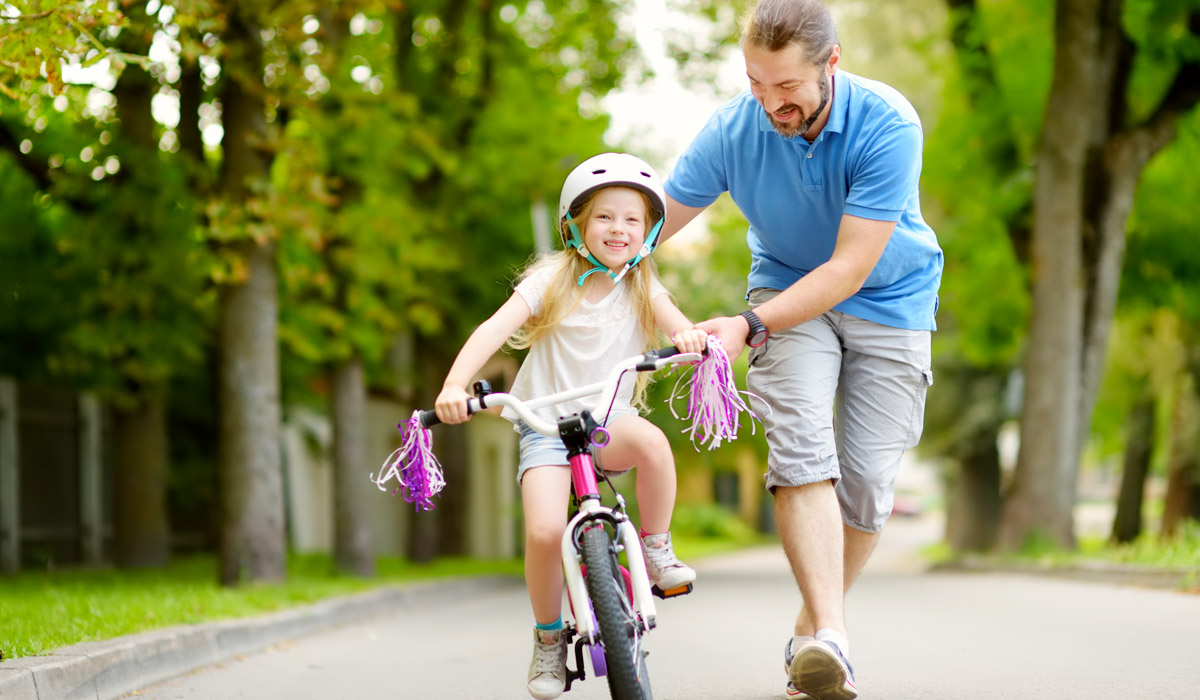 dad teaching daughter how to ride a bike