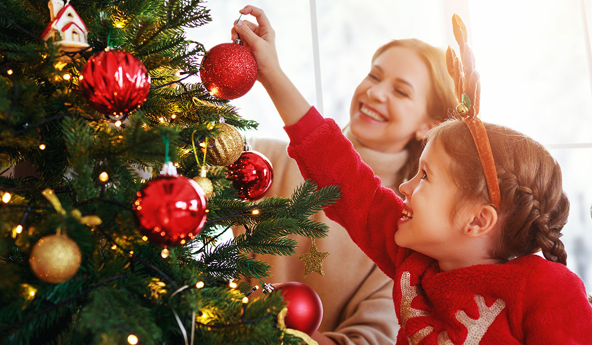 daughter helping mom with decorating christmas tree