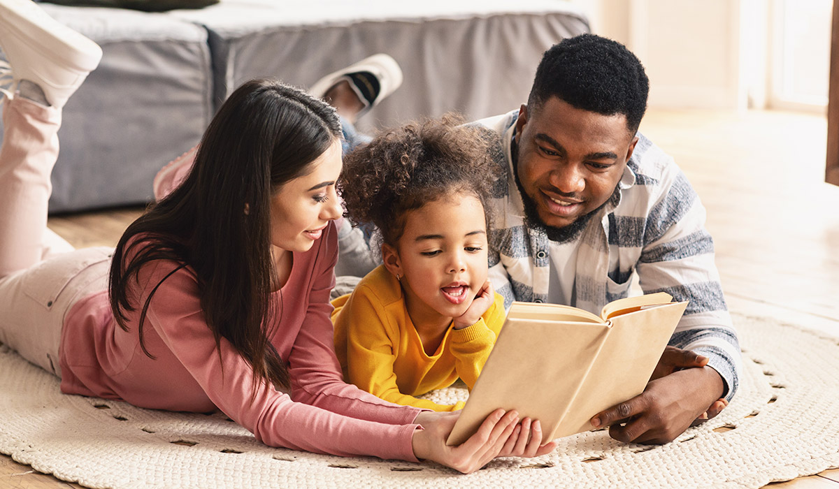 diverse family reading book on the floor