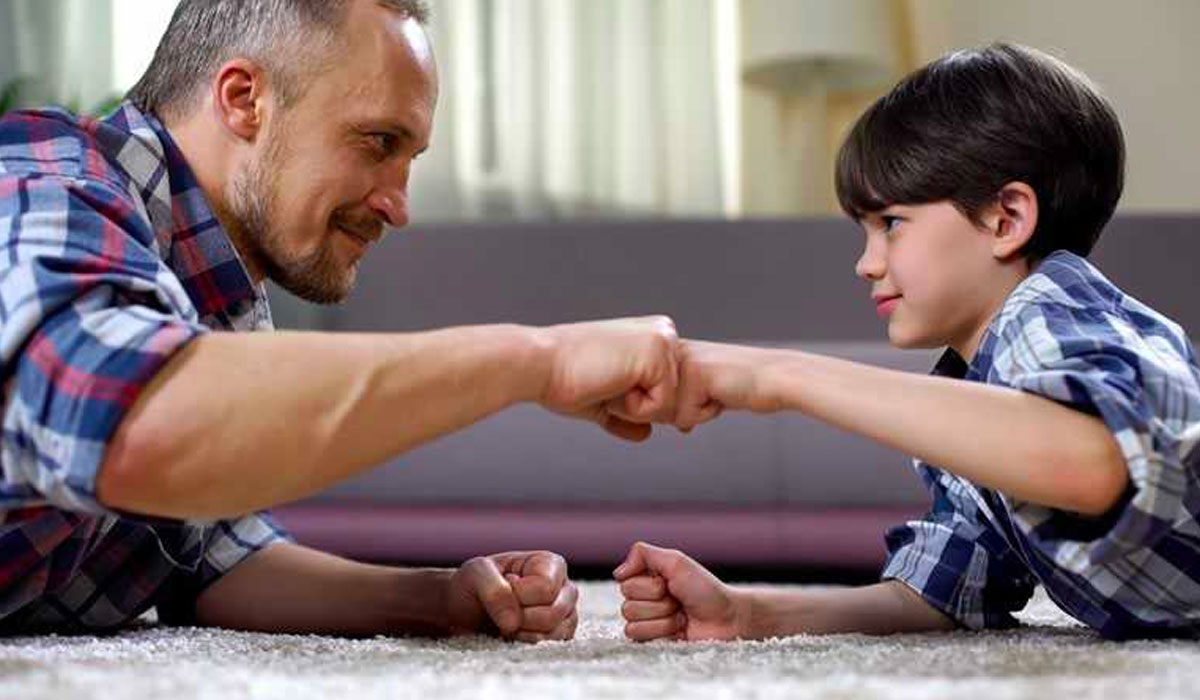 father and son fist bumping while lying on floor