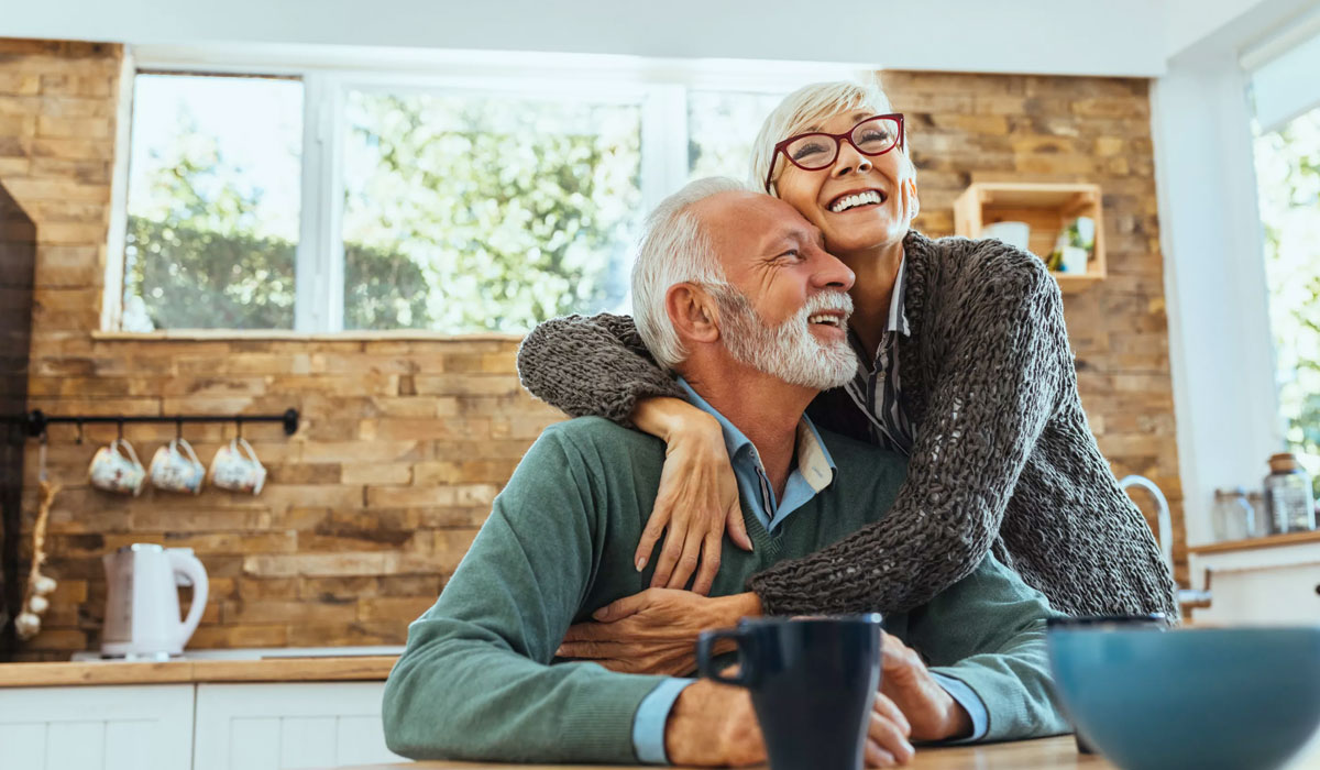 elderly couple embracing in the kitchen