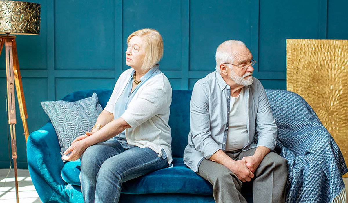 elderly couple sitting back to back in a blue room
