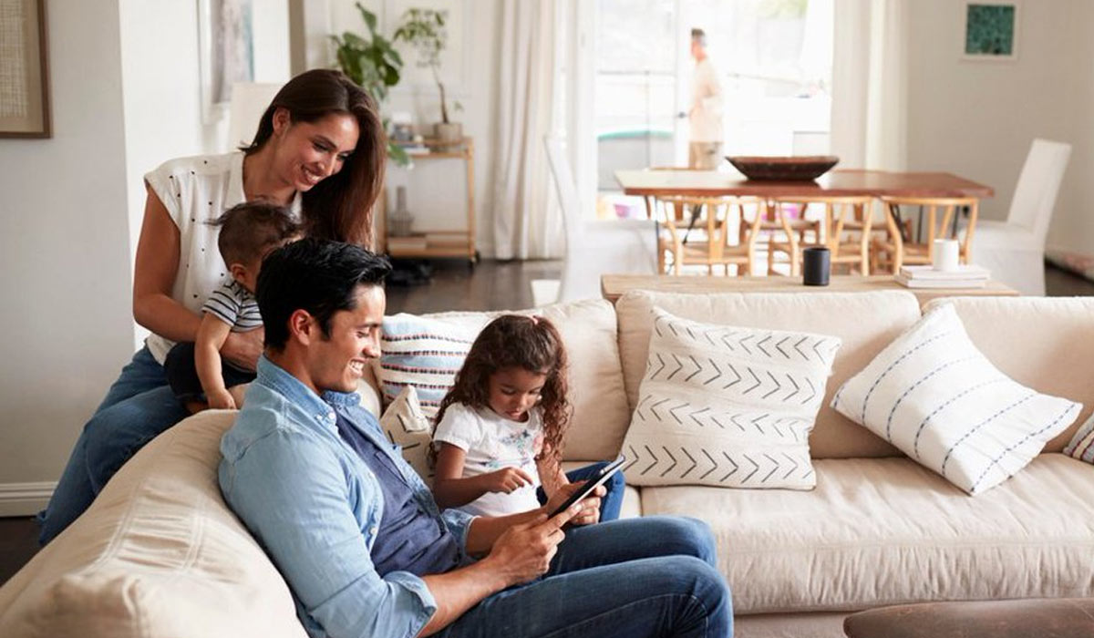 family sitting on sofa reading a book together in their living room