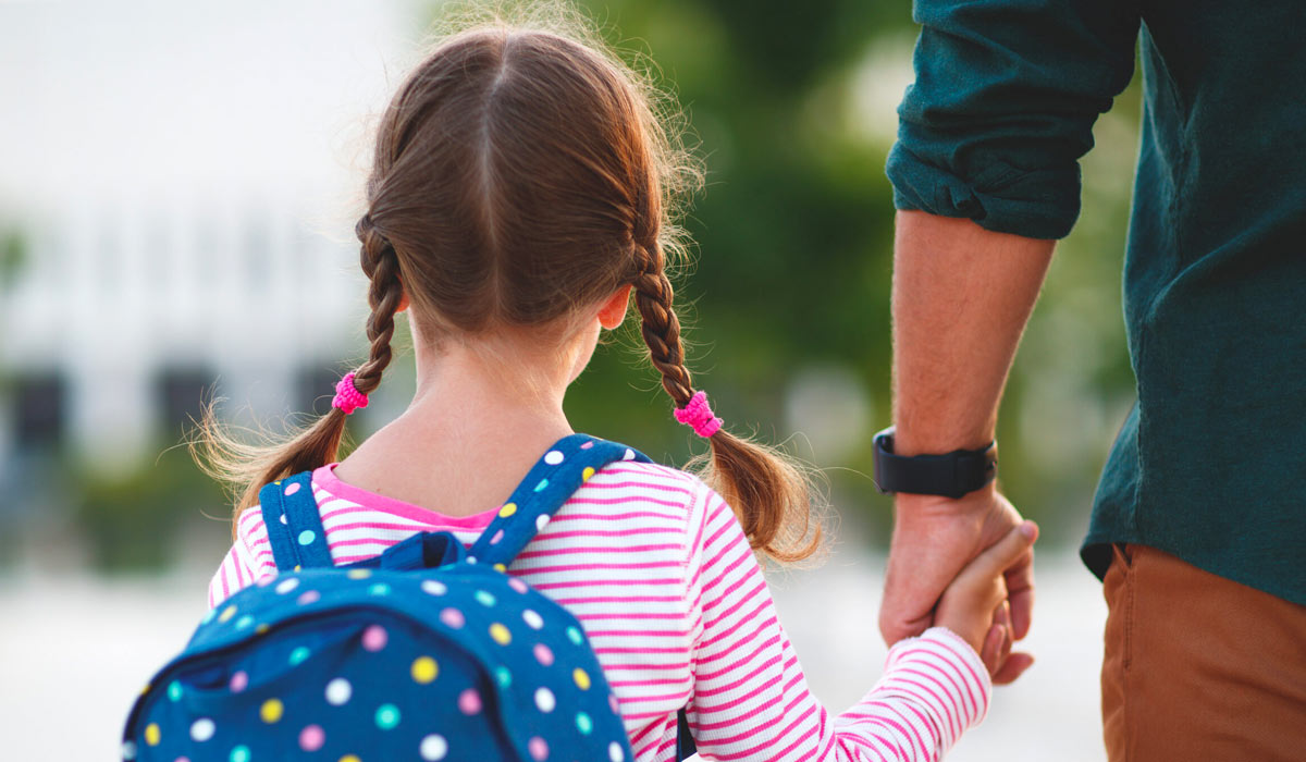 father holding daughters hand walking to school