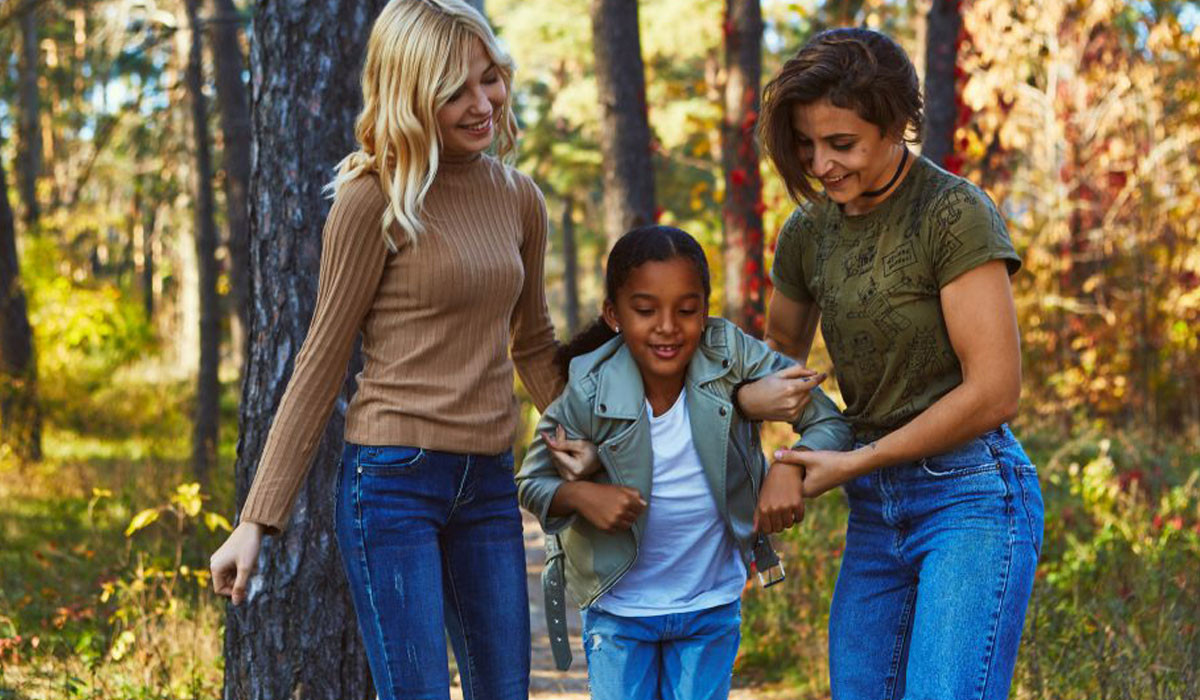 female couple with daughter walking in woods