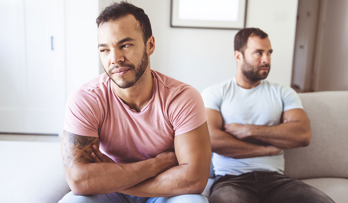 gay men folding their arms in frustration on couch with each other