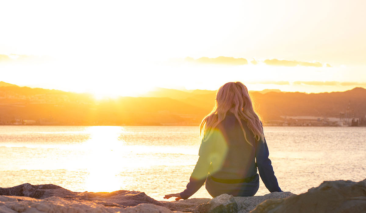 girl sitting alone facing sunset