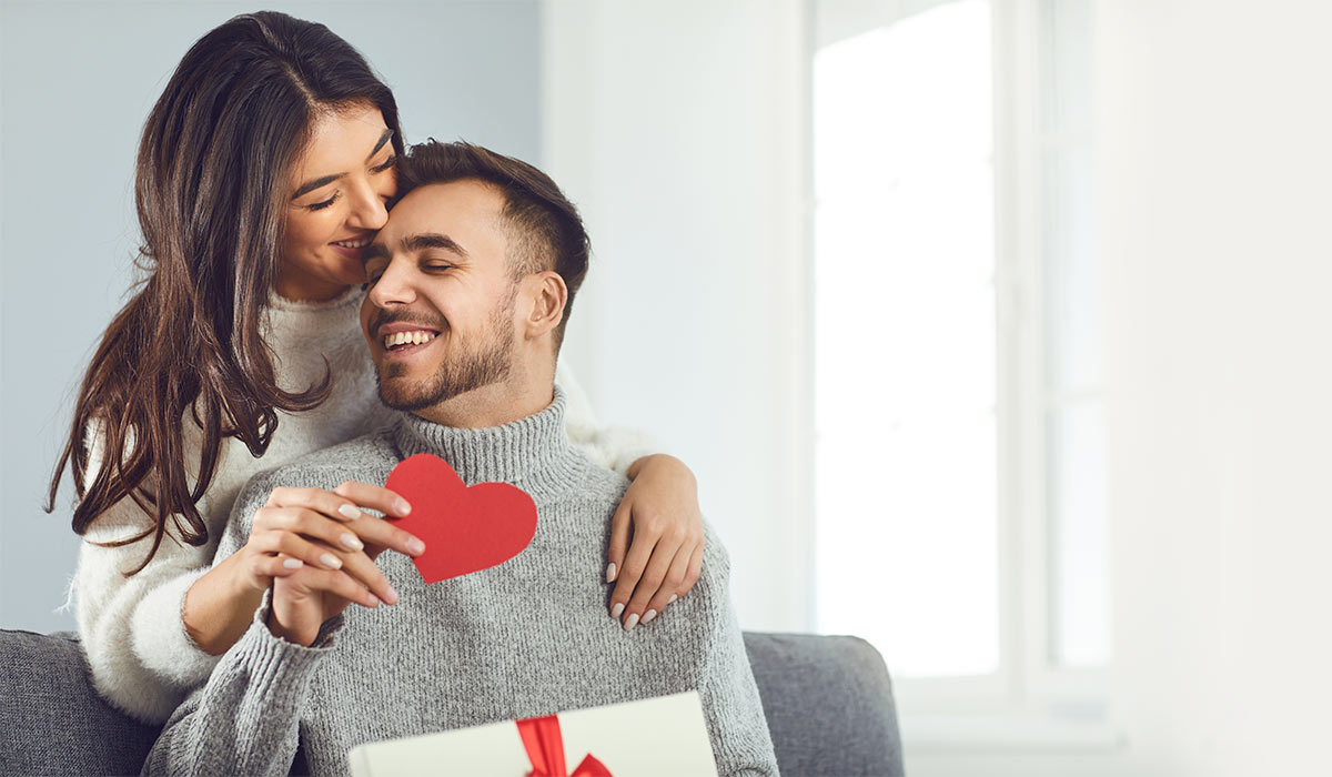 girlfriend gives heart to boyfriend on Valentines Day in a room