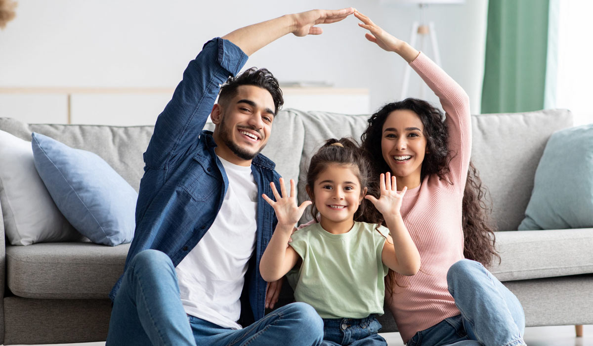 happy family sitting down and smiling in front of couch