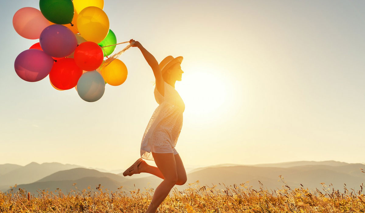 happy woman carrying colorful ballons across wheat field