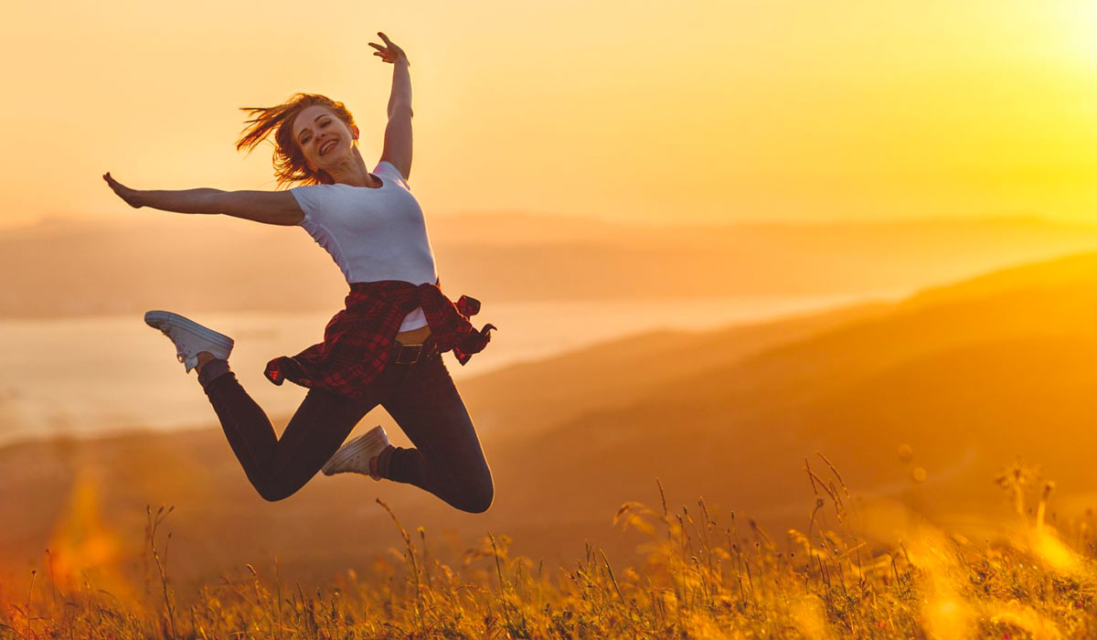happy woman jumping in the air in the fields