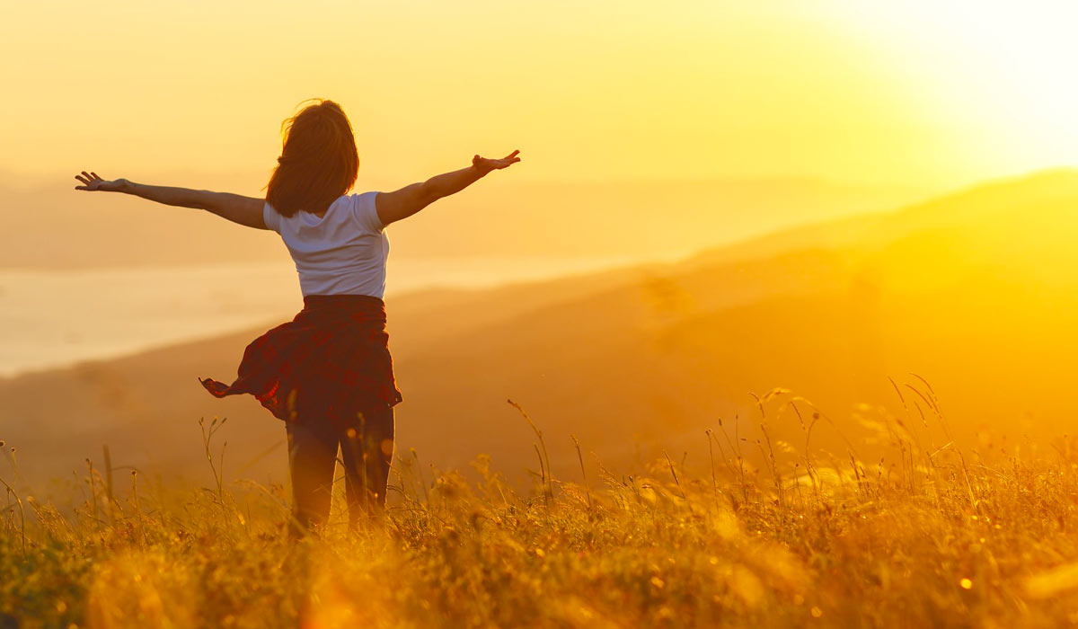 happy woman standing with her back on sunset in nature with open hands