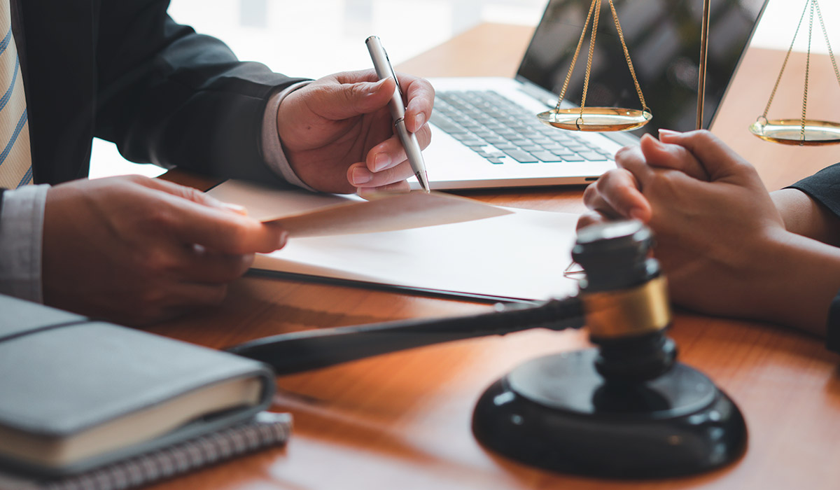 lawyer consulting with client with papers and gavel on desk