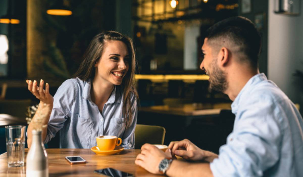 man and smiling woman having coffee together