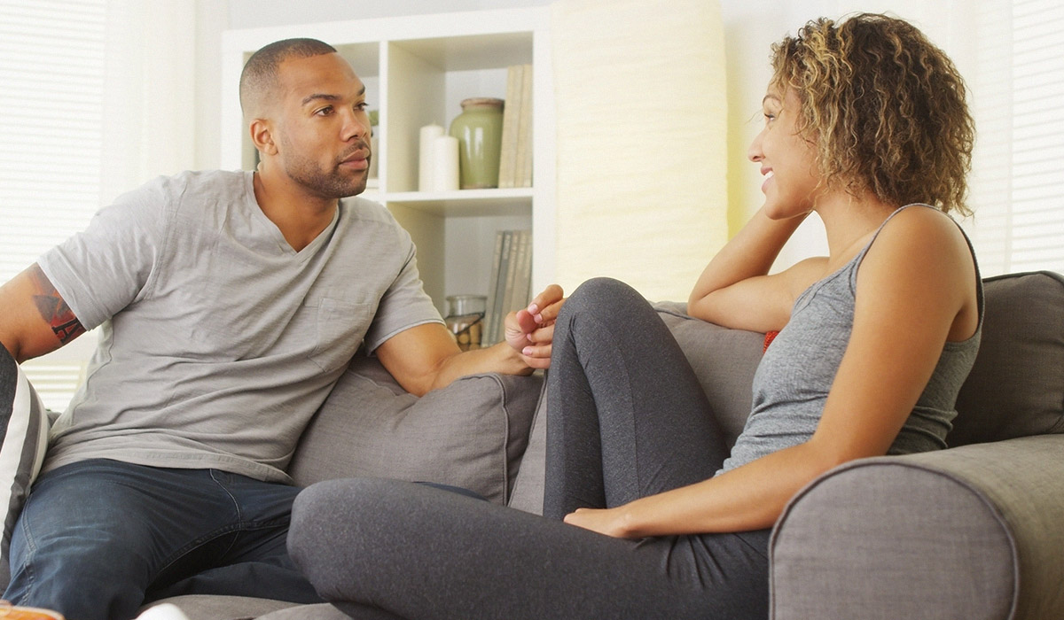 man and woman talking with each other on couch