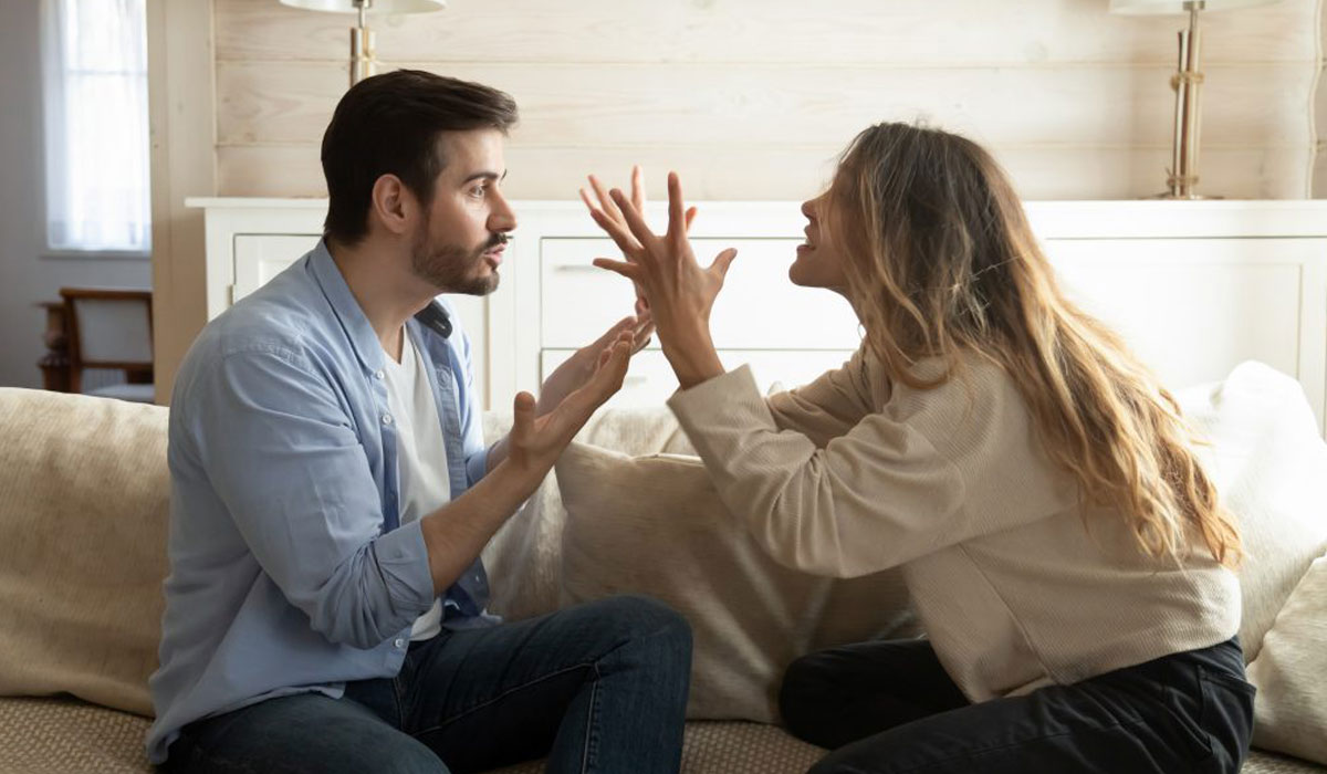 man and woman yelling at each other while sitting on couch