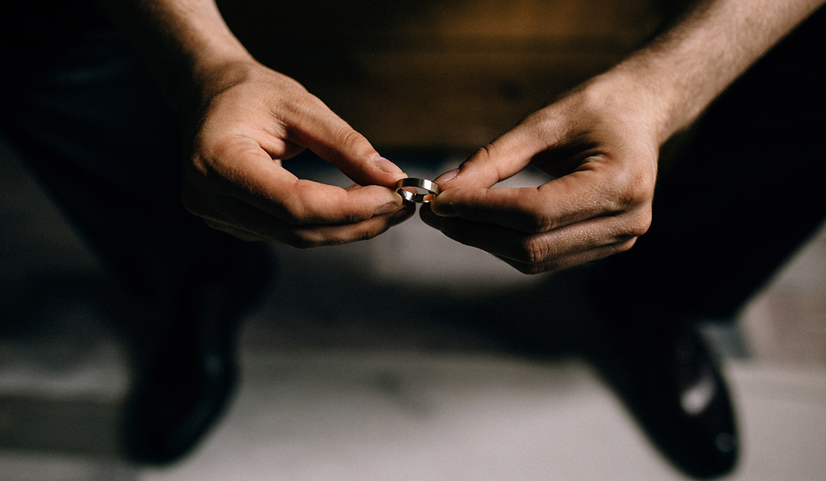 top down view of man holding wedding ring