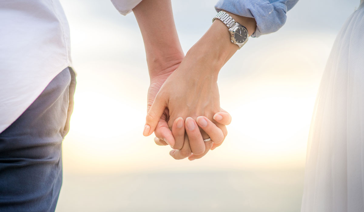 married couple holding hands in front of sunset