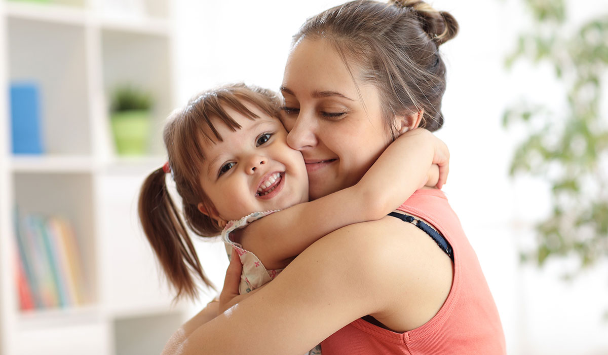 mom hugging smiling daughter