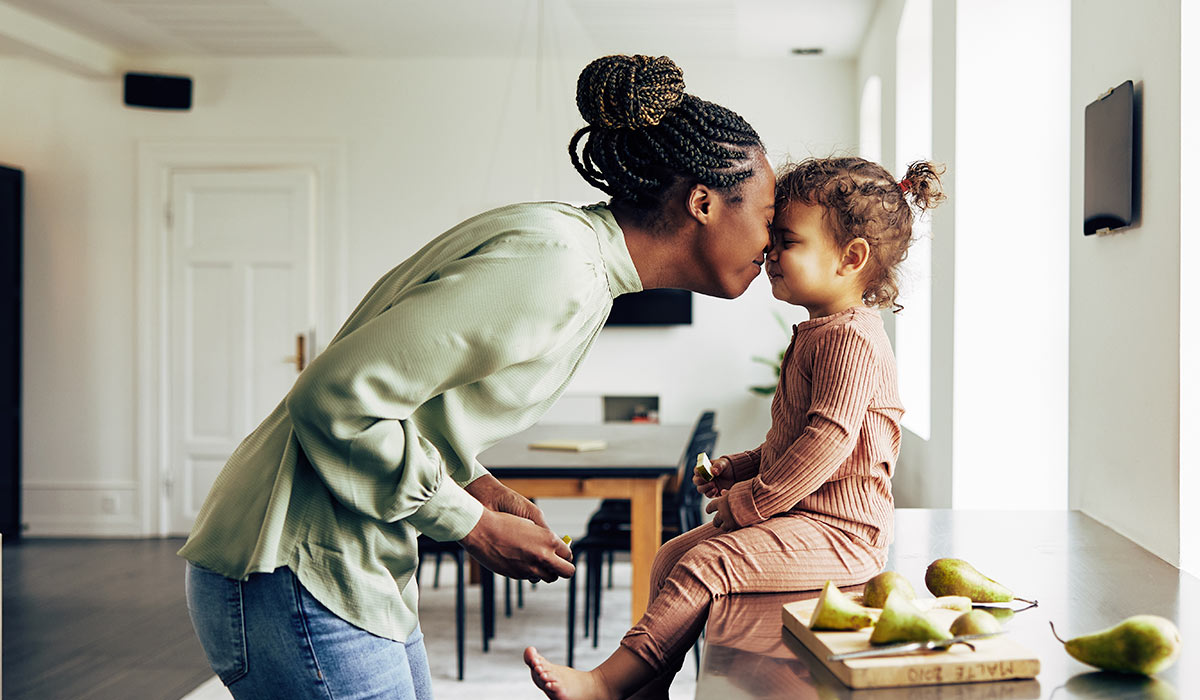 mom touching noses with her young daughter in the kitchen
