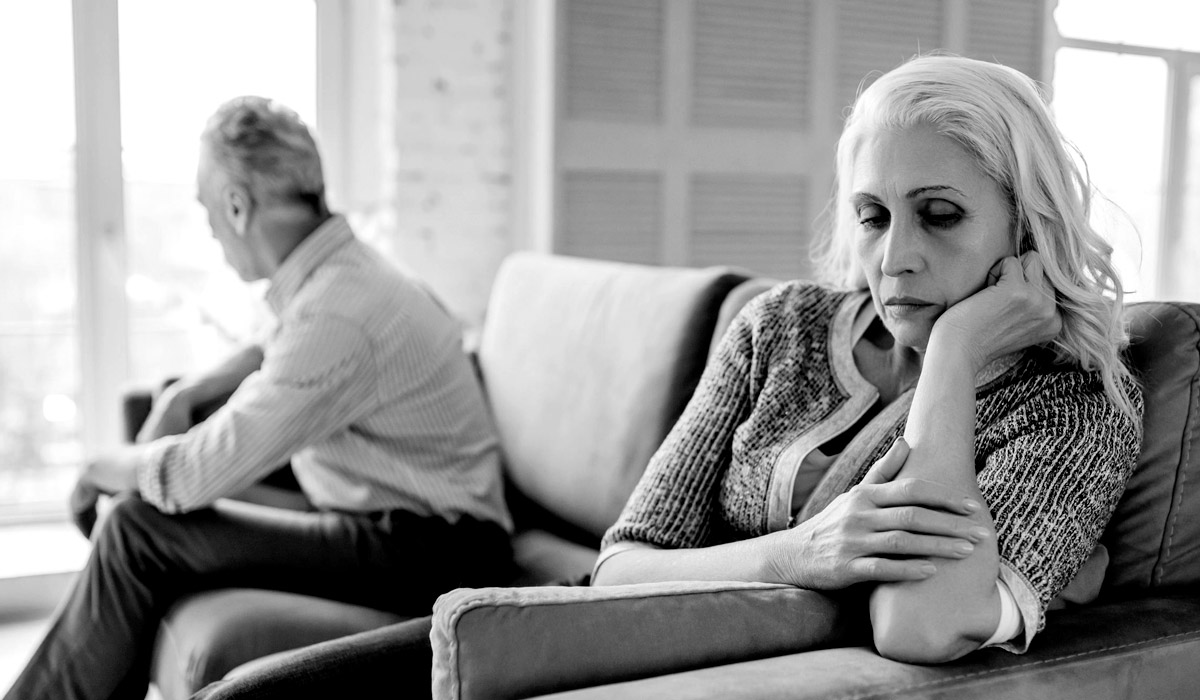 older woman sitting on couch looking away from older man
