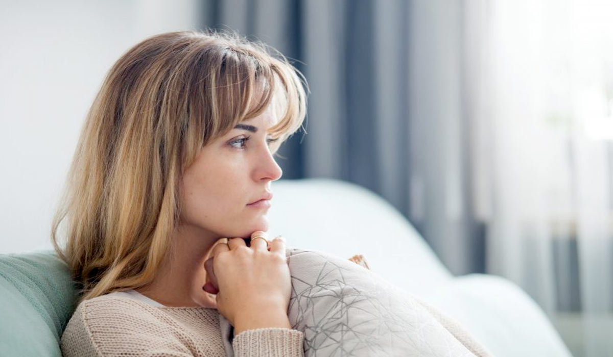 sad woman deep in thought sitting on couch