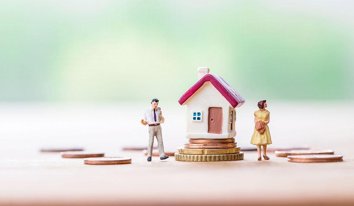selective focus of miniature angry woman with miniature man and mini house on stack coins over blurred background divorce concept