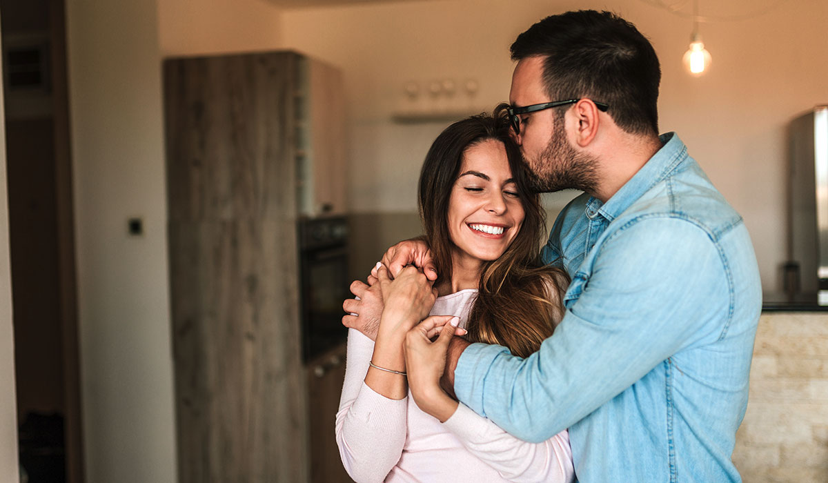 smiling woman embraced by husband giving a kiss to forehead