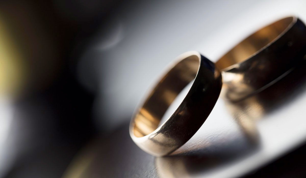 two wedding rings sitting on top of each other