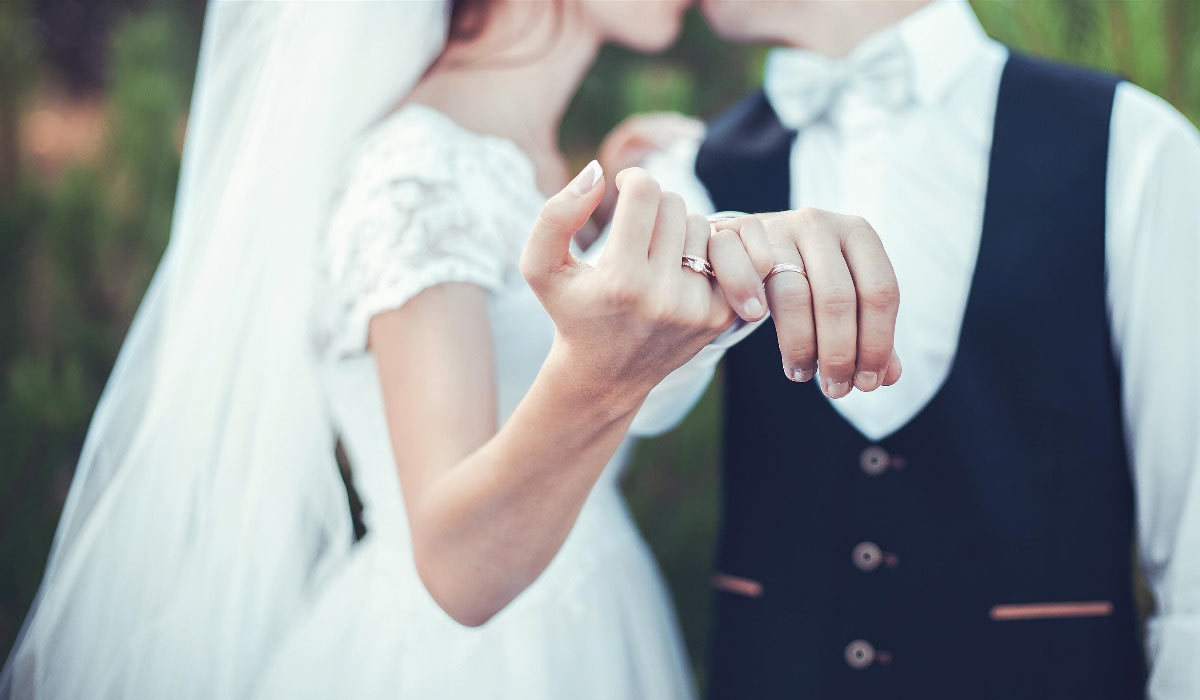 upclose of wedding rings worn by bride and groom