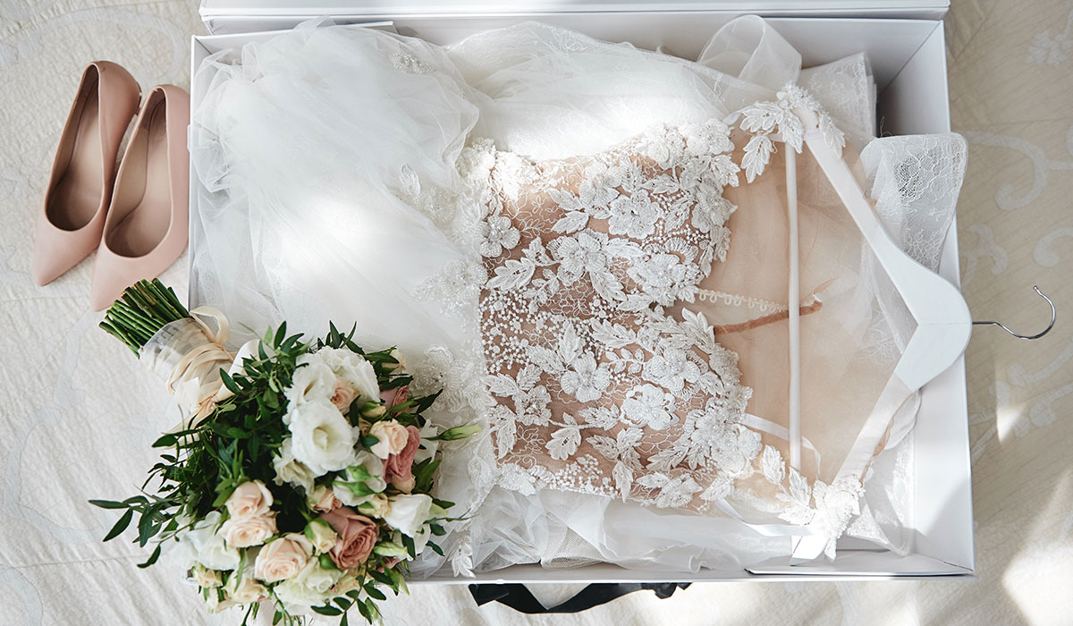 wedding dress in white box, beige shoes and bridal bouquet on bed